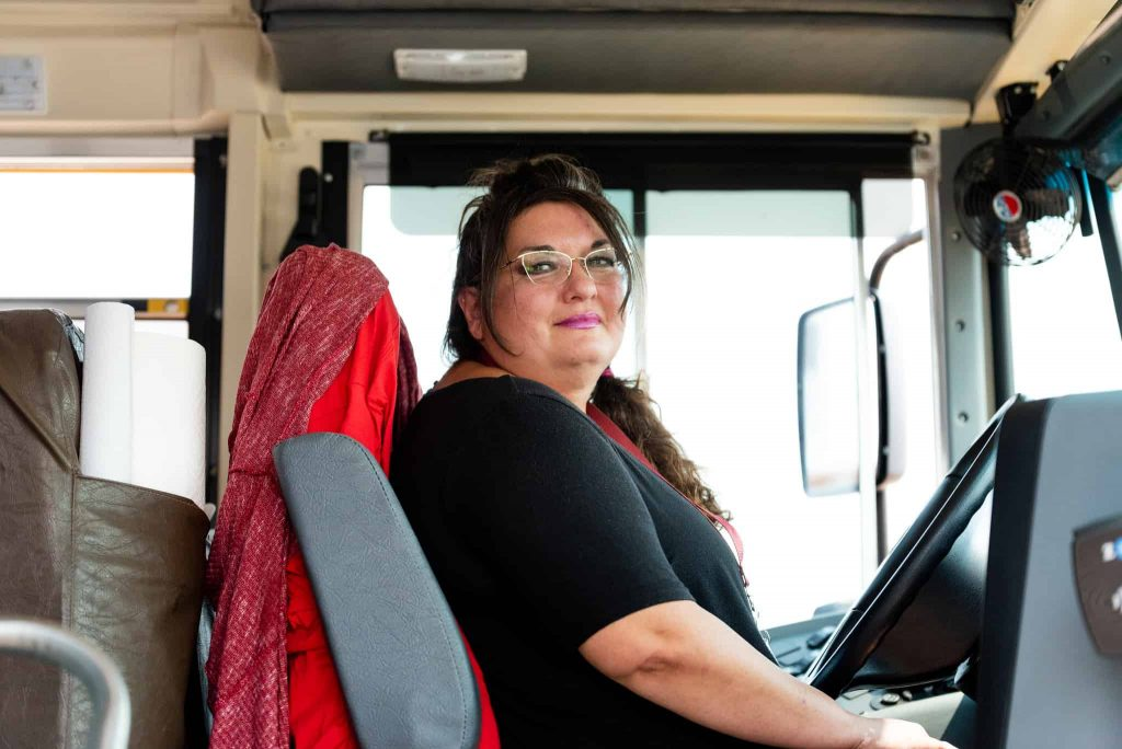 Bus driver Annette sitting in a school bus